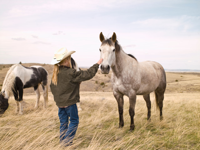 Young cowgirl petting horse on family ranch